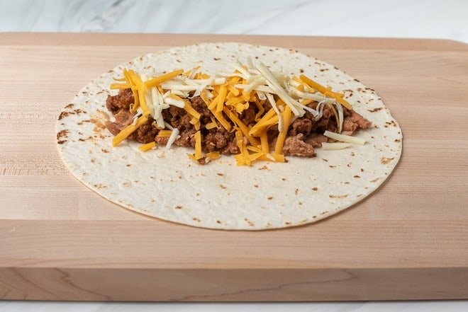 A tortilla topped with a beef and bean mixture and shredded cheese.