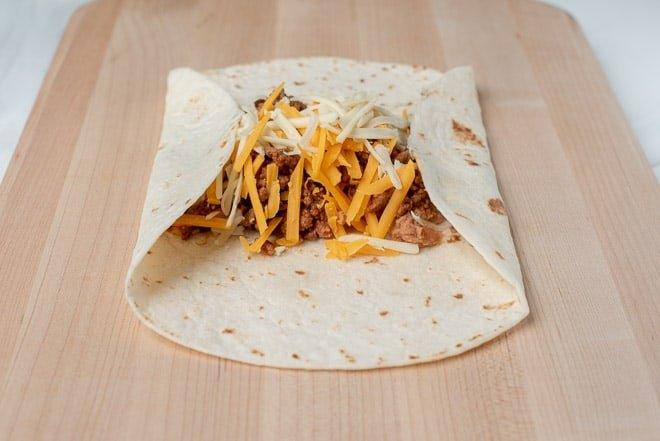A tortilla filled with beef, beans, and cheese is rolled up.