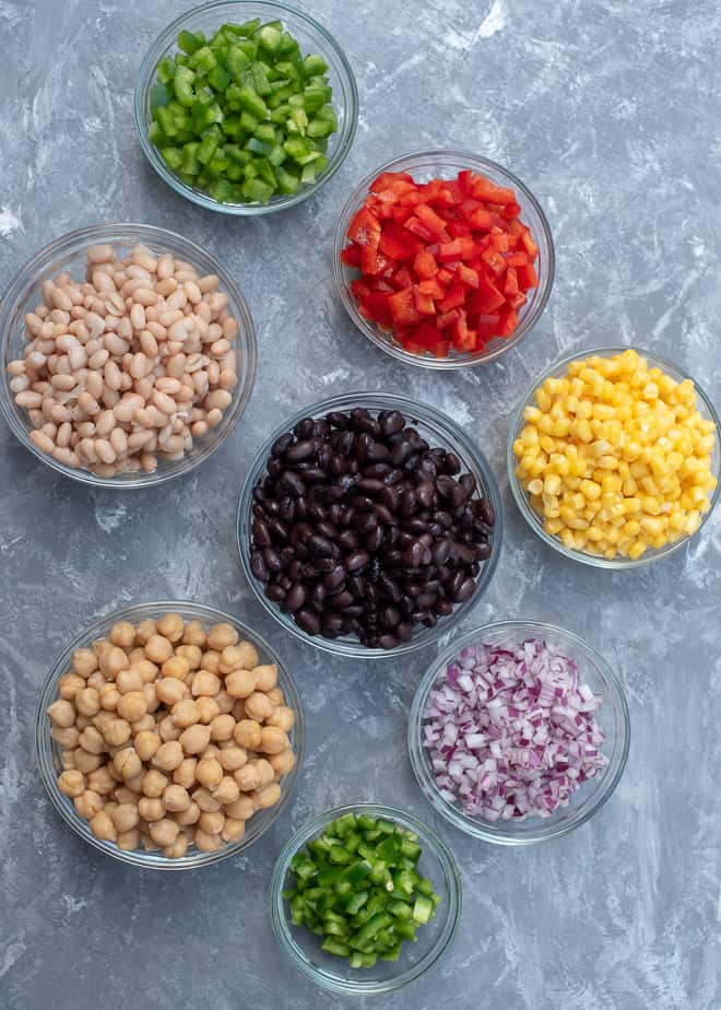 Beans, peppers, corn and red onion in small glass bowls.