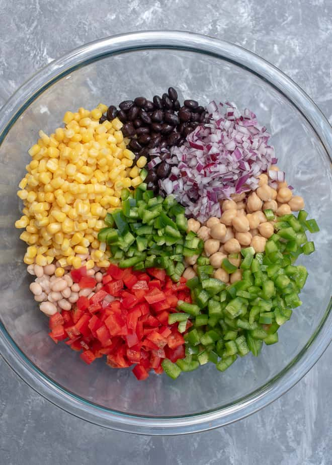 Beans, red onion, peppers, and corn in a large glass mixing bowl.