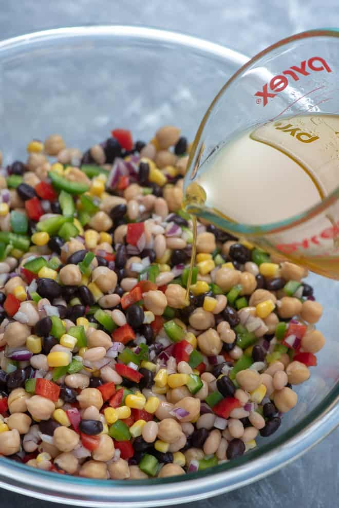 Pouring the dressing into the bowl of Mexican Three Bean Salad.