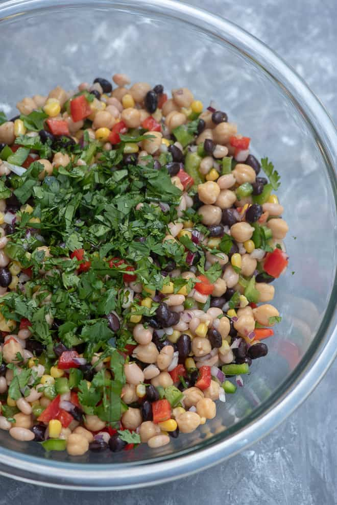 Mexican Three Bean Salad in a large glass mixing bowl topped with chopped cilantro.
