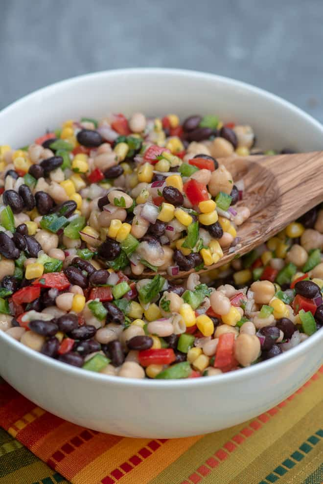 A bowl filled with a colorful bean salad.
