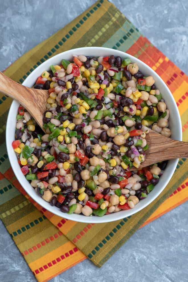 Mexican Three Bean Salad in a white serving bowl on a colorful cloth with wooden spoons in it.