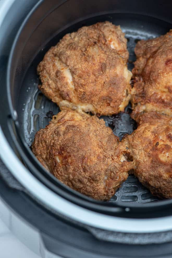 Four pieces of fried chicken in the air fryer insert.