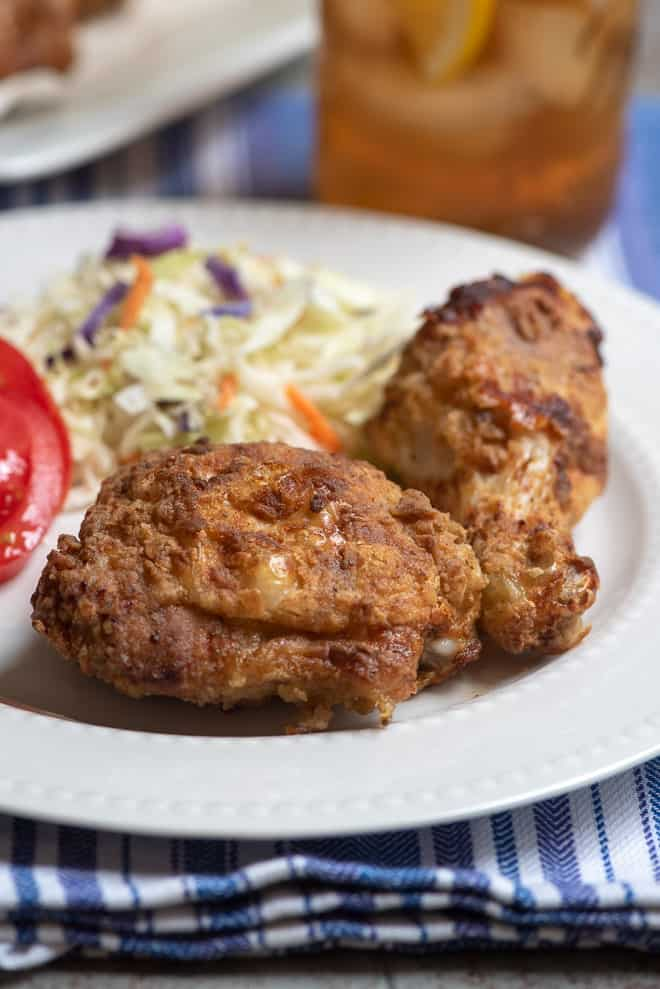 Air Fryer Fried Chicken on a white serving plate with coleslaw.