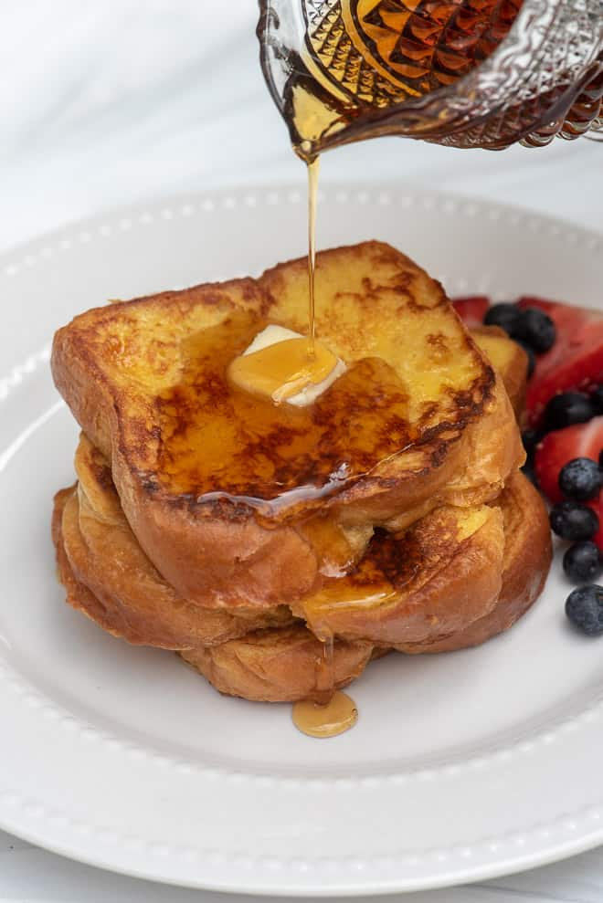 Brioche French Toast on a white plate with maple syrup being poured on top.