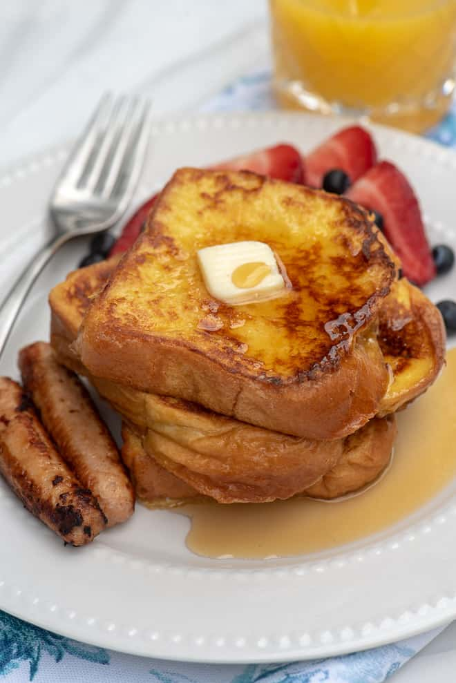French toast on a white plate with a pat of butter and maple syrup.