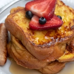 A close up shot of Brioche French Toast with fresh berries and maple syrup.