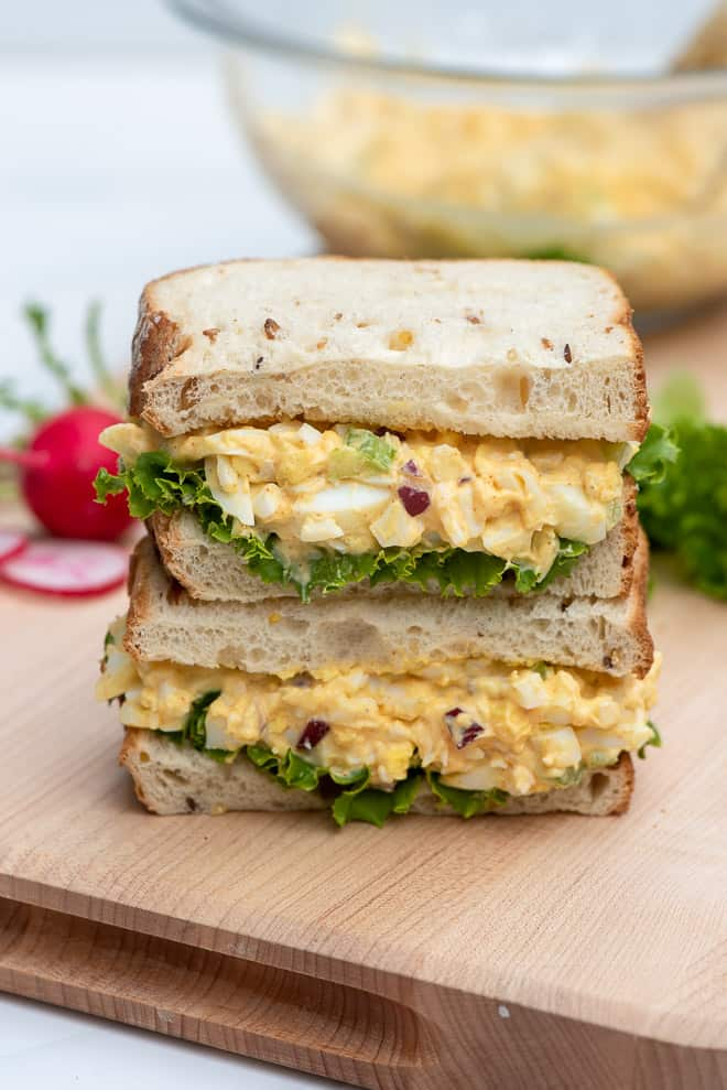 An egg salad sandwich cut in half and stacked.