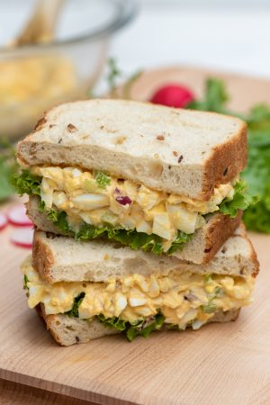An egg salad sandwich cut in half and stacked on a cutting board.