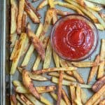 French fries on a baking sheet with a small bowl of ketchup.