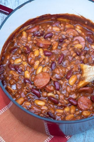 A pot of beans with kielbasa being stirred with a wooden spoon.
