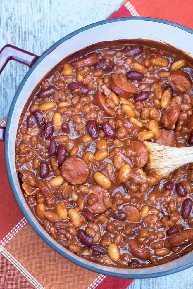 A Dutch oven full of kielbasa and beans from over the top.