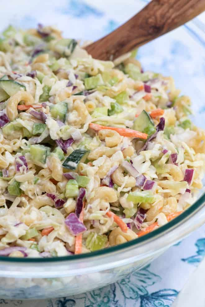 A close up image of Macaroni Coleslaw in a glass serving bowl.