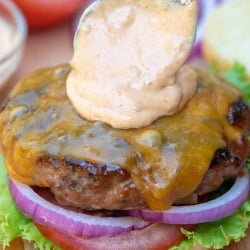 A close up of a spoon adding sauce to a burger.
