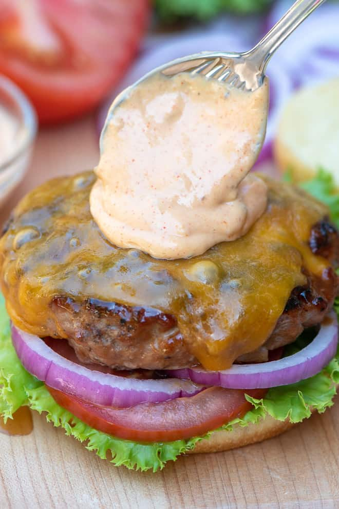 A burger being topped with a spoonful of Awesome Burger Sauce
