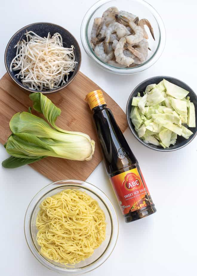 The ingredients - Sweet soy sauce (kecap manis), cooked yellow egg noodles, baby bok choy, bean sprouts, shrimp, and green cabbage.