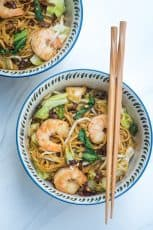 A bowl with shrimp and noodles with chopsticks lying over the top.