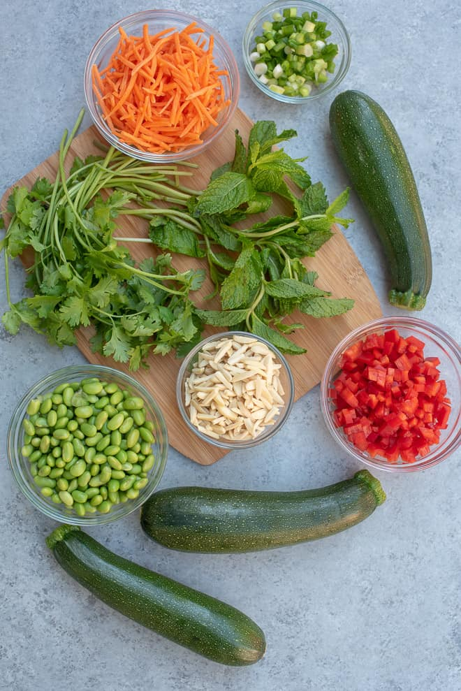 The Ingredients in Asian Zucchini Noodle Salad on a grey board.
