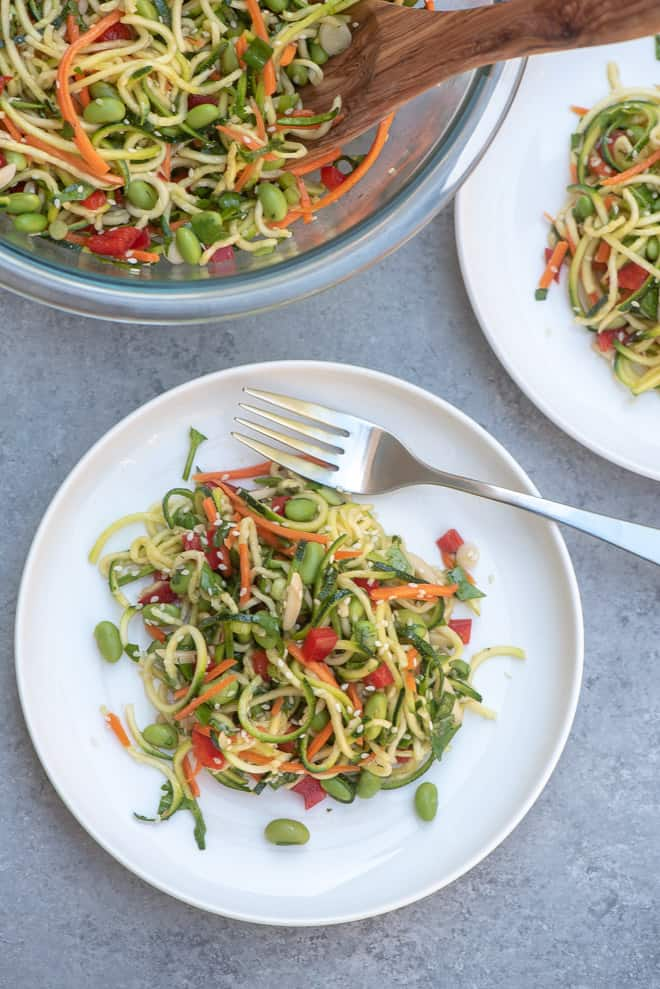 Asian Zucchini Noodle Salad on a white plate with a fork with the serving bowl in the background.