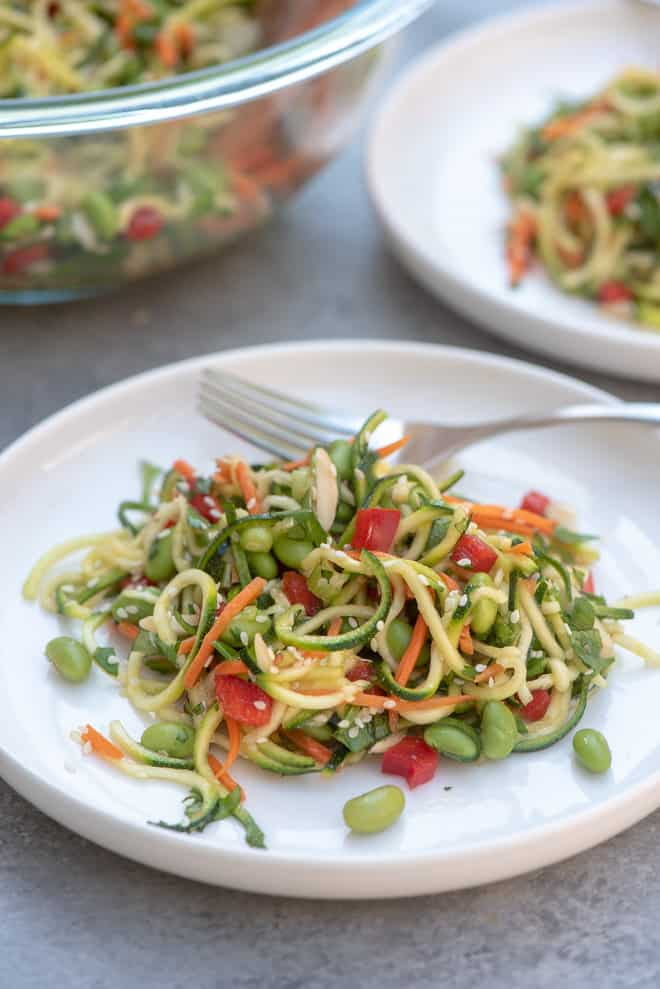 Asian Zucchini Noodle Salad on a white plate with a fork.