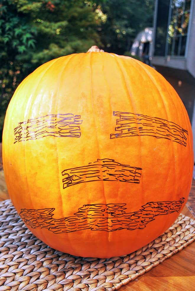 A large pumpkin with a face drawn on it.