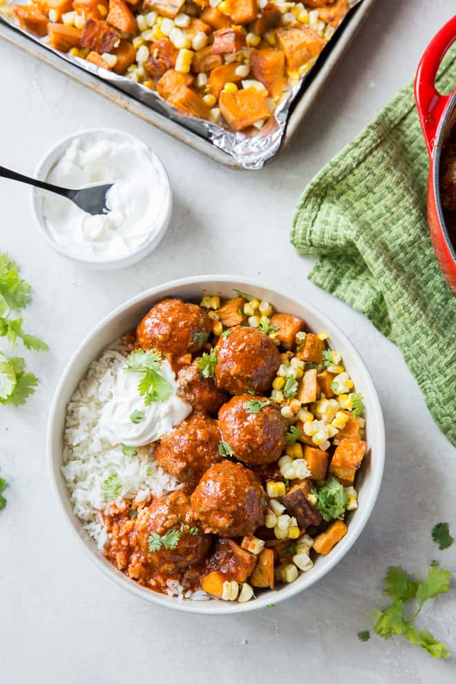 Tex-Mex Meatballs in a white bowl over rice with sweet potatoes and corn shot from over the top.