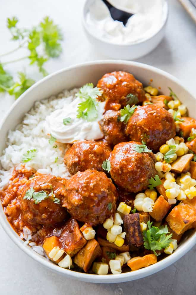 Tex-Mex Meatballs in a white bowl over rice with sweet potatoes and corn.