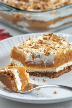 A sliced of layered pumpkin dessert with a fork on a white plate.