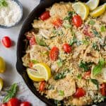 A skillet filled with orzo, chicken, grape tomatoes, and slices of lemon.