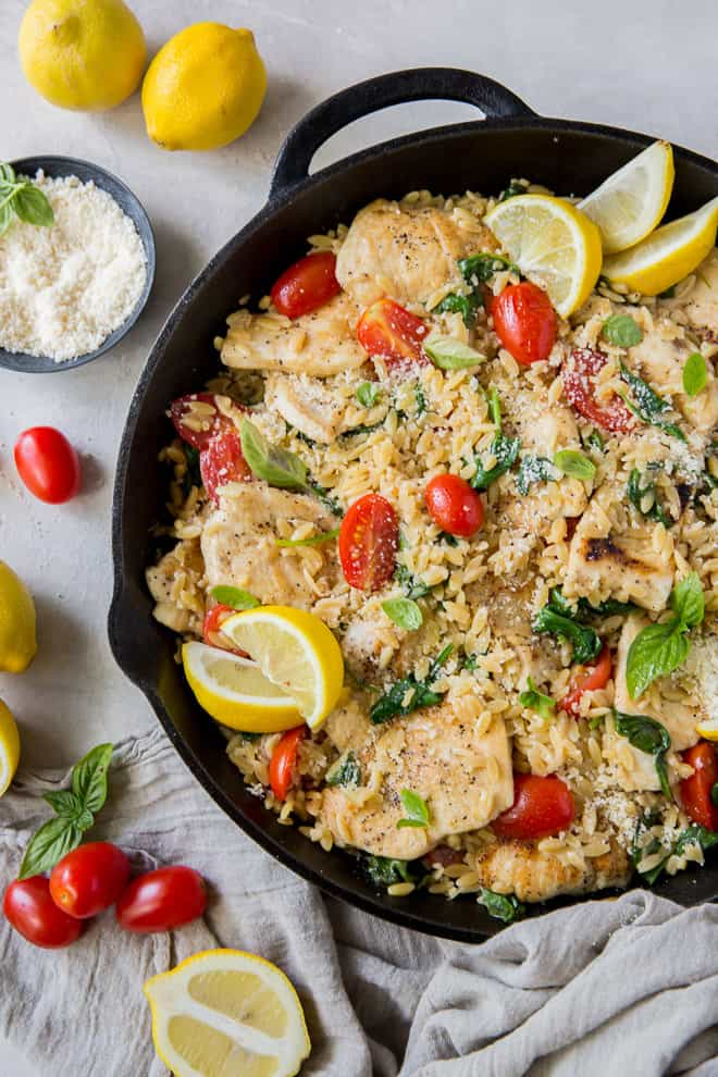 Lemon Chicken with Orzo in a skillet with lemons and Parmesan cheese placed around it.