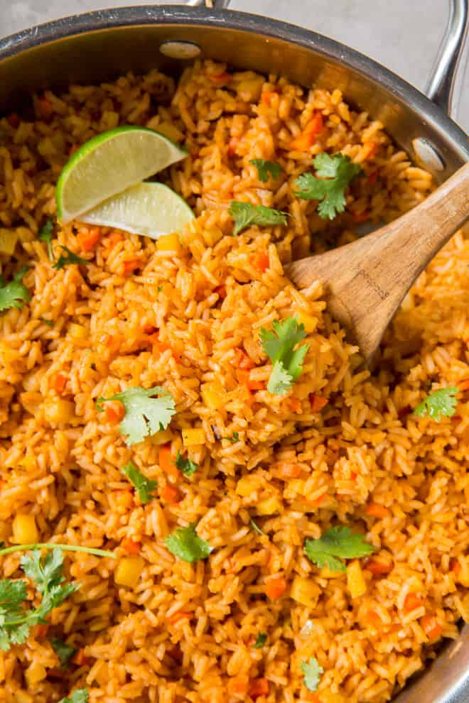 A close up of Mexican Rice in a skillet with a wooden spoon.