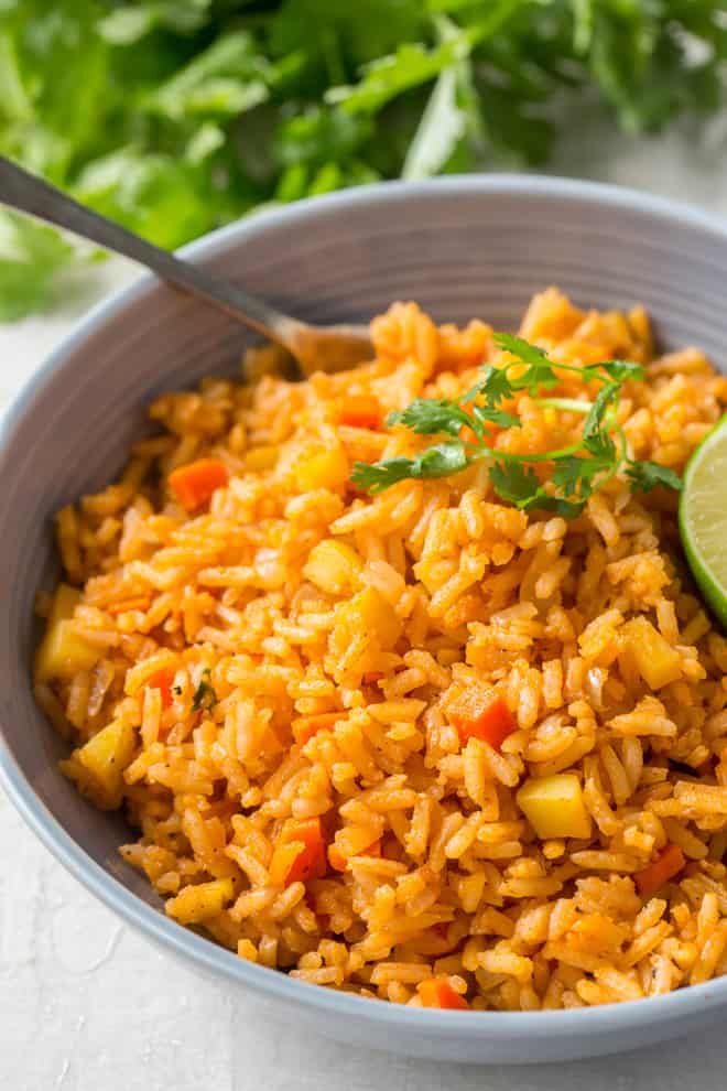 A serving of Restaurant Style Mexican Rice in small bowl with a fork.