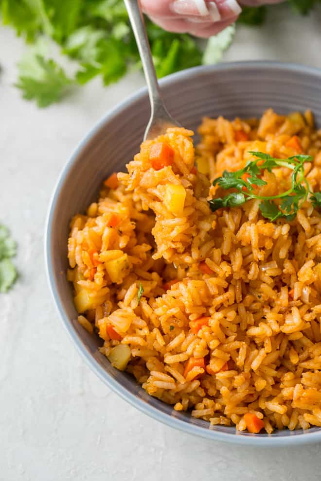 A fork lifting out of a bowl of Restaurant Style Mexican Rice.