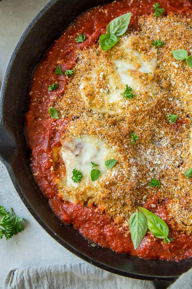 A close up shot of a cast iron skillet full of Chicken Parmesan
