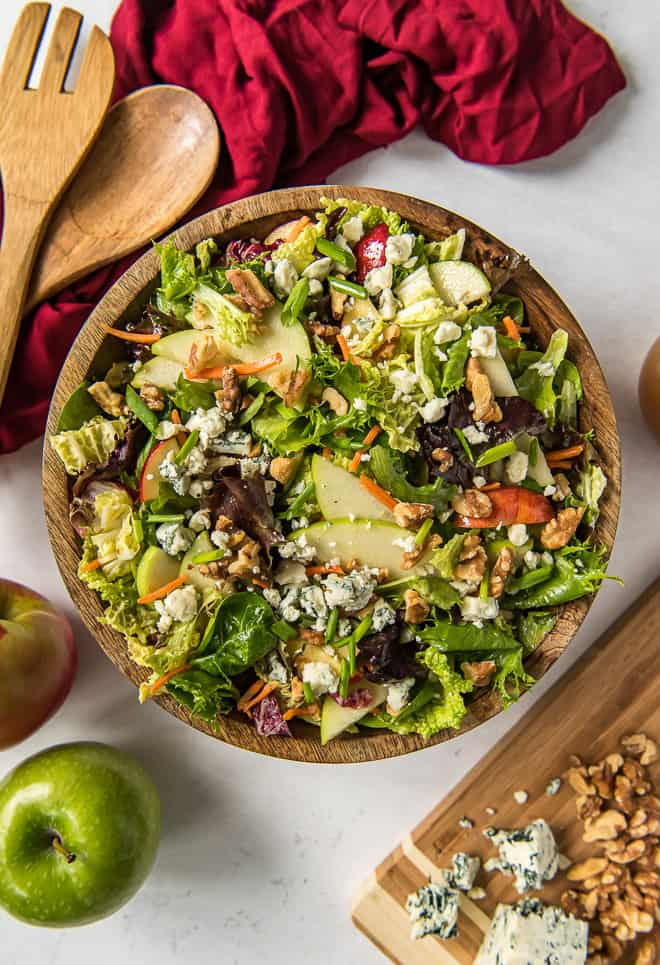 A wooden salad bowl filled with Apple Cabbage Salad with Walnuts and Gorgonzola with salad serving spoons nearby.