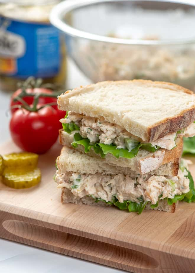 A chicken salad sandwich on a cutting board with pickles and tomatoes.
