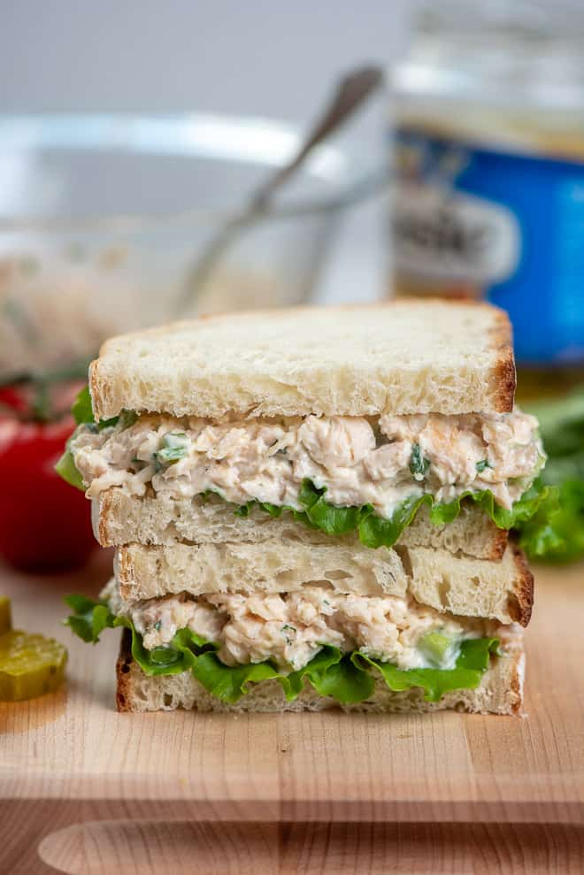 A close up image of a chicken salad sandwich cut in half and stacked on a cutting board.