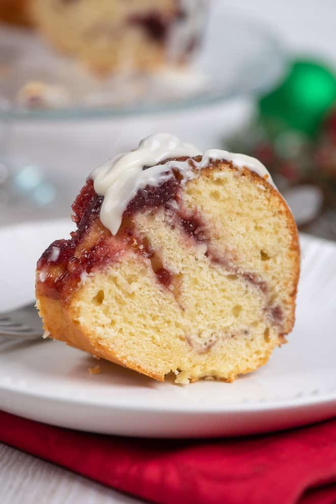A slice of Cranberry Swirl Bundt Cake on a small white serving plate.