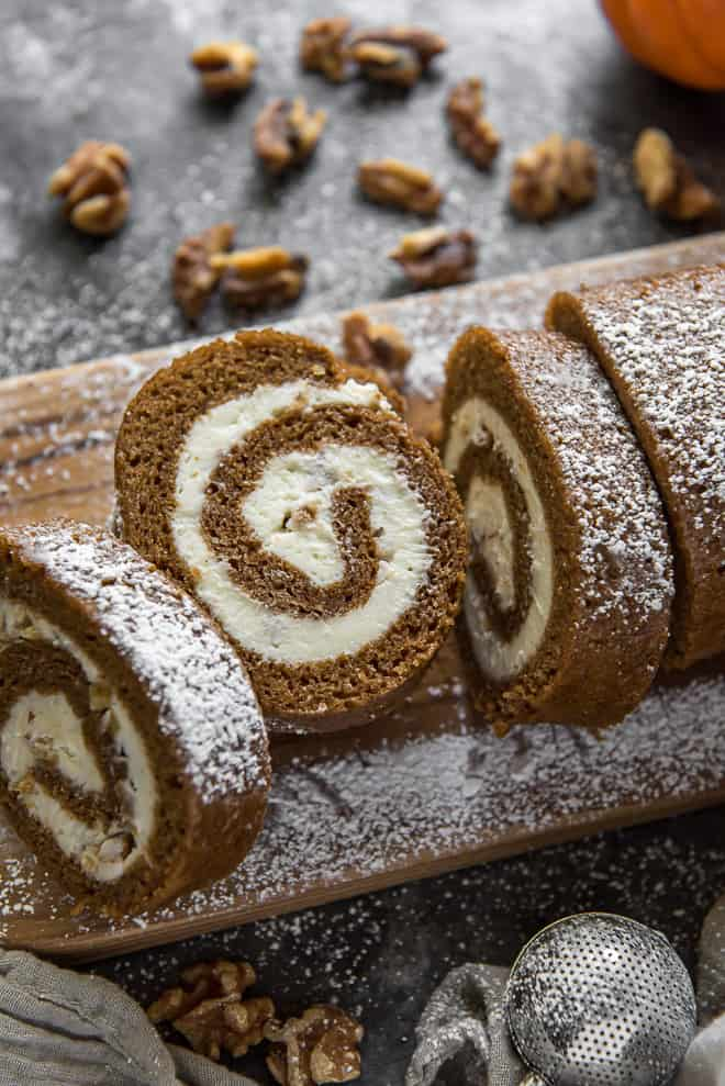 Sliced Pumpkin Roll with Cream Cheese Walnut Filling on a narrow wooden cutting board.