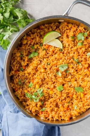 A skillet filled with Mexican rice, cilantro and slices of lime.