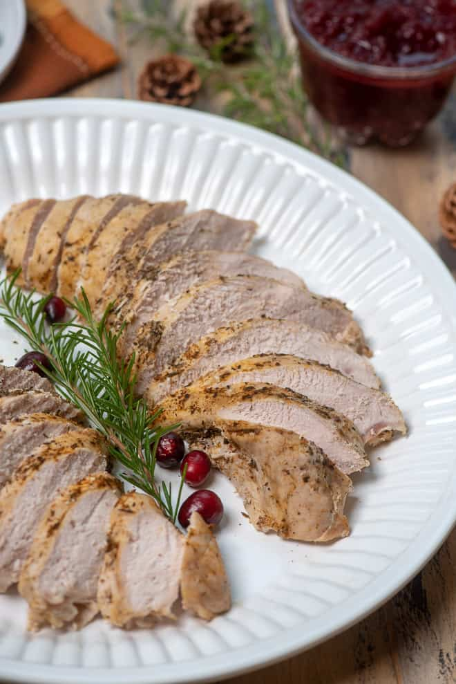 A white platter with sliced Slow Cooker Turkey Breast garnished with fresh rosemary and cranberries.