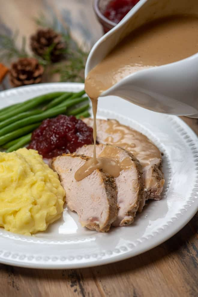 Gravy being poured over slices of turkey on a plate with mashed potatoes.