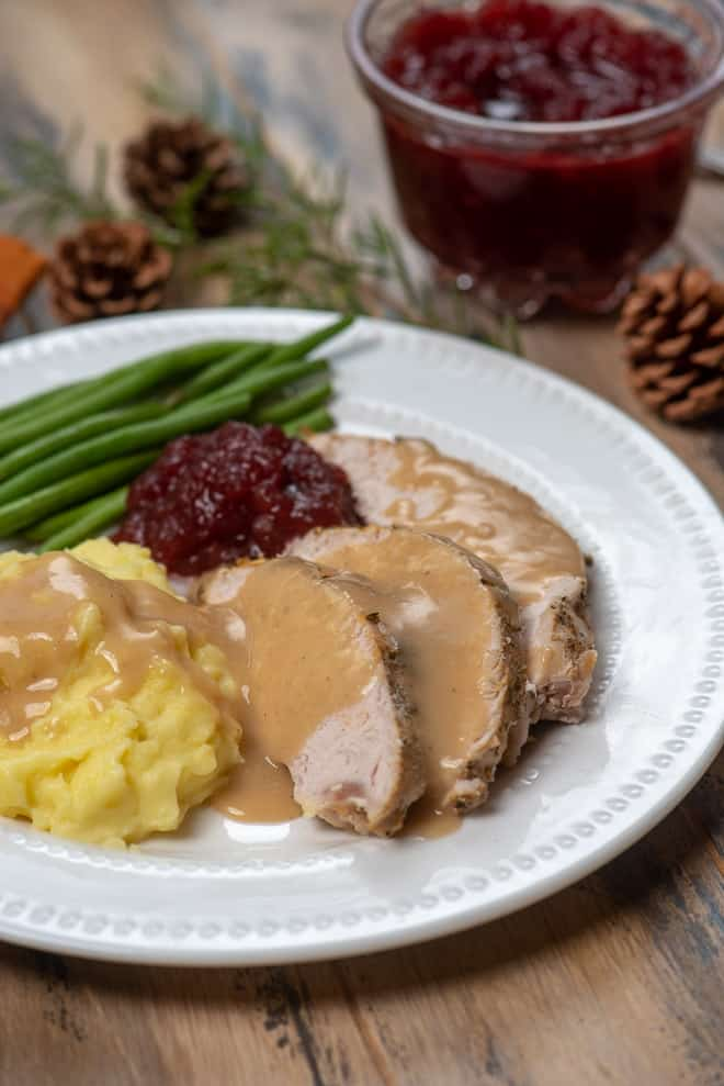 Slow Cooker Turkey Breast with Gravy on a white plate with mashed potatoes, cranberry sauce and green beans.