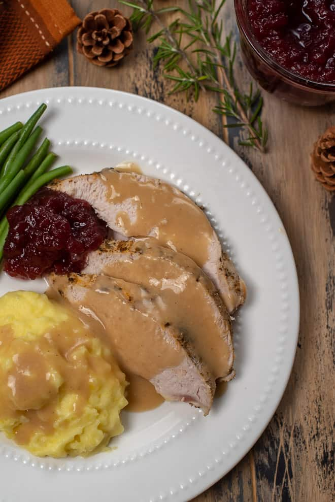 A white plate with Slow Cooker Turkey Breast with Gray, mashed potatoes, cranberry sauce and green beans.