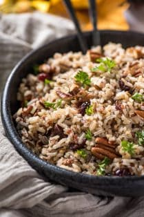 A black bowl filled with wild rice and pecans.