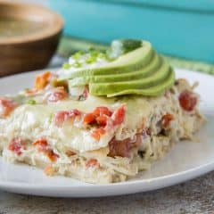 A slice of chicken tortilla casserole topped with slices of avocado on a white plate.