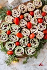 A pretty tray full of sliced tortilla pinwheels with grape tomatoes and parsley.