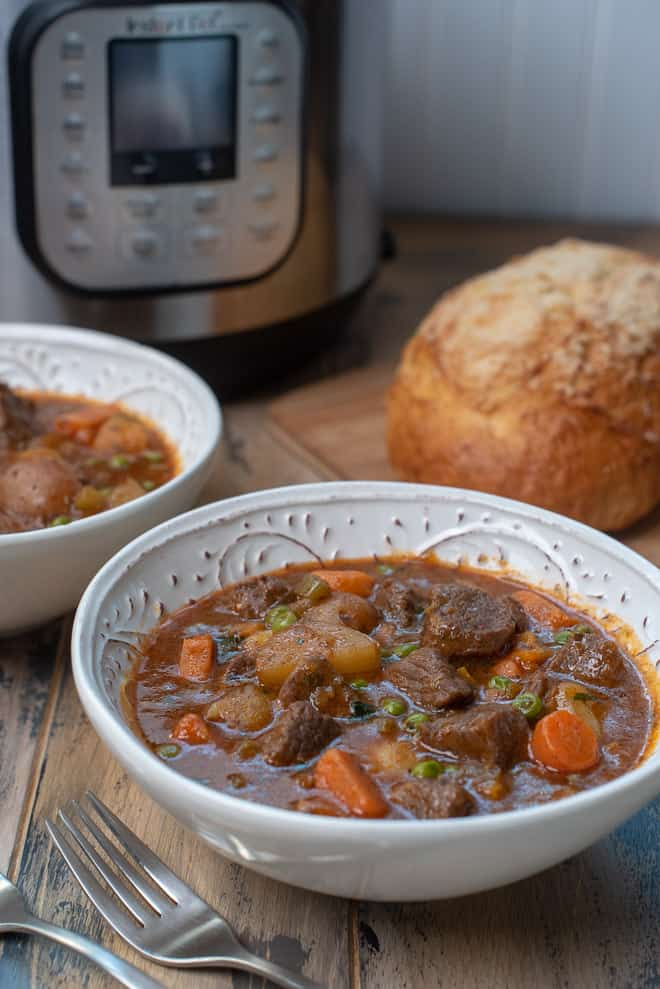 White serving bowls of beef stew with an Instant Pot and French bread in the background.